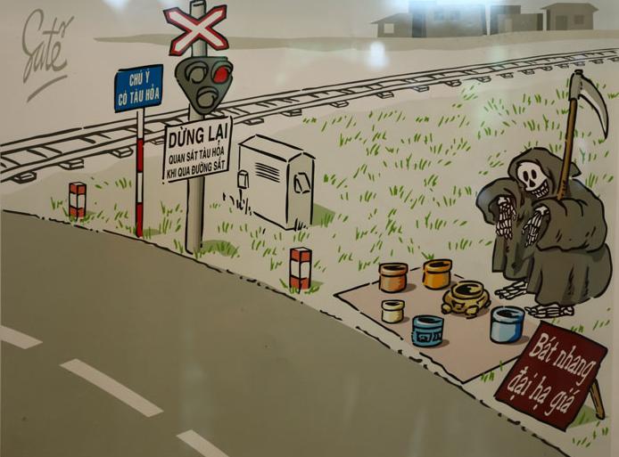 """Hình vẽ với thông điệp khi đi qua đường ray cần phải nhìn trước sau và đi chậm kẻo dễ gặp """"thần chết"""""""